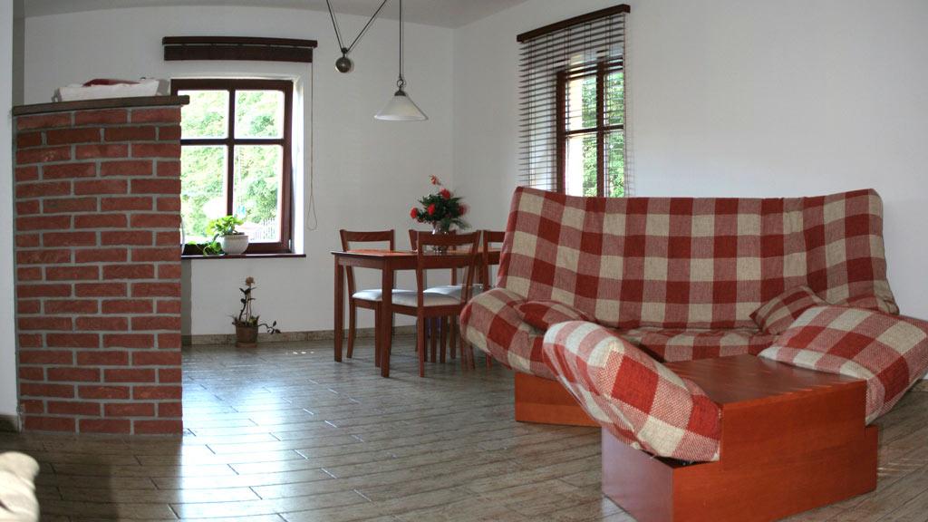 Rozkládací pohovka posezení a kuchyňský kout v levé garsoniéře.