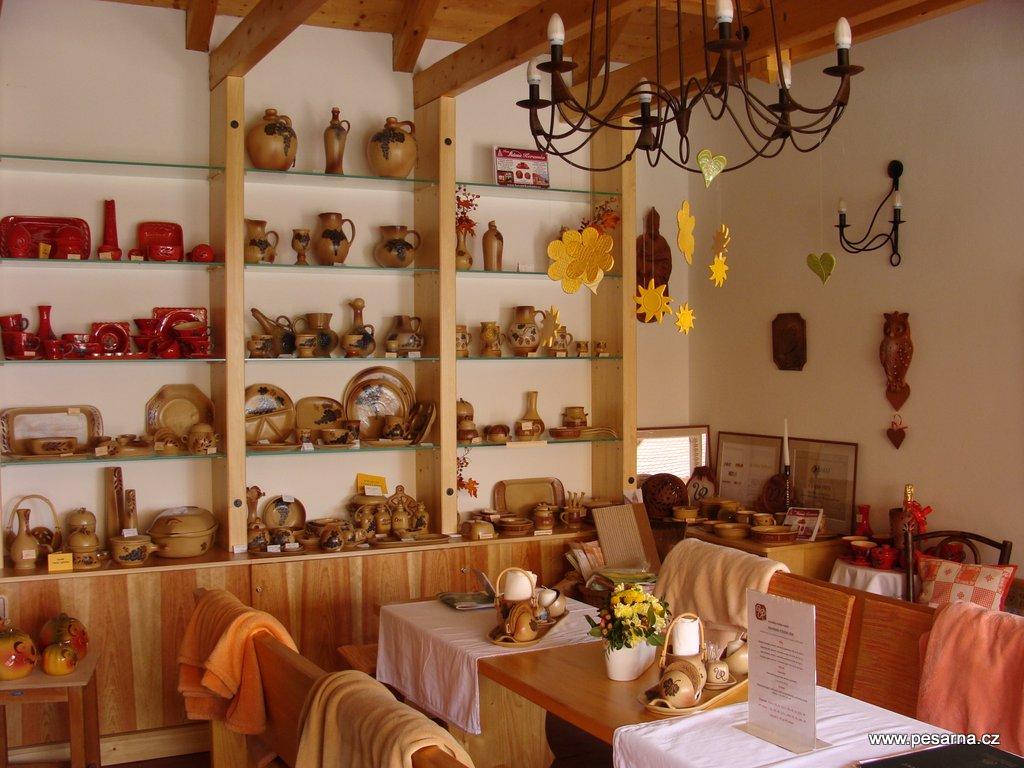 Místa k sezení v interiéru vinotéky a nabídka keramiky.